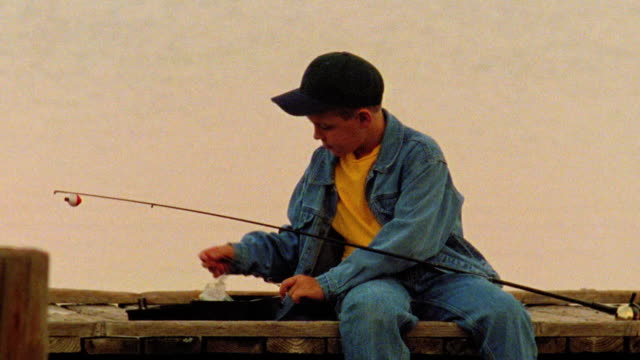 close up PAN boy sitting down on dock with fishing pole + tackle box + preparing to fish