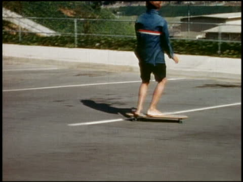 1965 close up boy skateboarding / medium shot tracking shot 2 boys in blue jackets skateboarding barefoot in parking lot / Pacific Palisades High School, Los Angeles, California