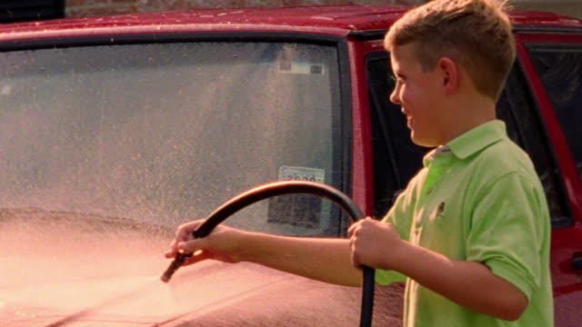 close up boy spraying suv with hose rinsing off soap - washing stock videos & royalty-free footage