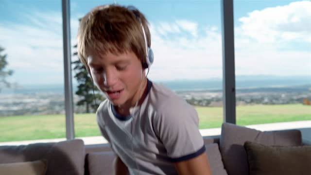 Close up boy wearing headphones and dancing in front of window / Somerset West, South Africa