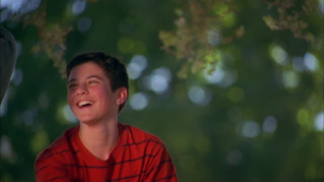 close up boy wearing red shirt pushing boy on tire swing in yard - tire swing stock videos & royalty-free footage