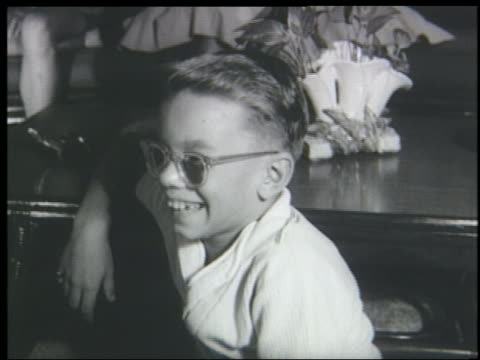 b/w 1961 close up boy with eyeglasses sitting in living room watching television + laughing - 1961 stock videos & royalty-free footage