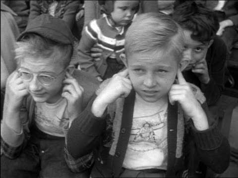 vídeos de stock e filmes b-roll de b/w 1948 close up boys in audience holding ears / documentary - orelha