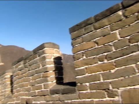 Close up bricks / long shot pan of Great Wall of China with mountains in background
