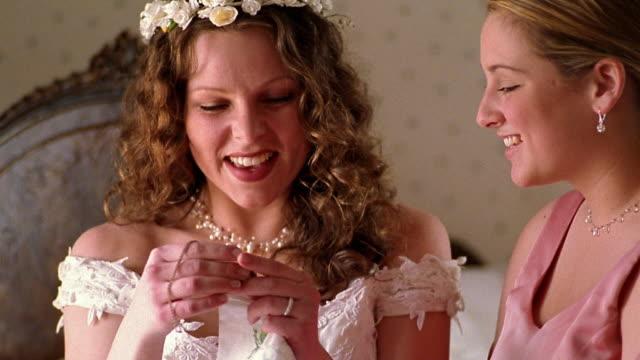 Close up bride looking at locket necklace / bride and bridesmaid hugging