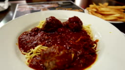 Close up brooklyn spaghetti meatballs and fries on table