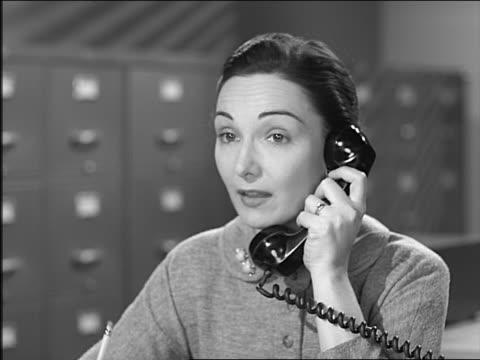 b/w 1957 close up brunette woman in office at desk talking on telephone - 1957 bildbanksvideor och videomaterial från bakom kulisserna