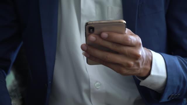 vídeos de stock e filmes b-roll de close up business people using smart phone with shopping - sobre os ombros vista traseira