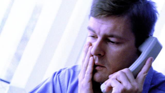 vídeos de stock, filmes e b-roll de blue close up businessman at desk talking on telephone looking stressed / tilt down hand tapping on desk - superexposto
