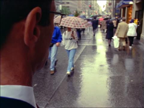 rear view close up businessman checks watch + walks away on sidewalk as time lapse people walk past him - 腕時計点の映像素材/bロール