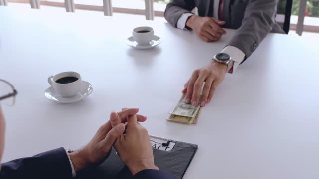 stockvideo's en b-roll-footage met dicht zakenman hand over omkopen geld naar een ander businessman.businessman rekening geld pak en ondertekenen van een contract in onderhandeling teken vergadering van project contract. corruptie concept - omkoping