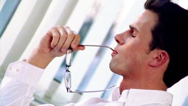 OVEREXPOSED CANTED close up businessman holding eyeglasses + checking watch in office