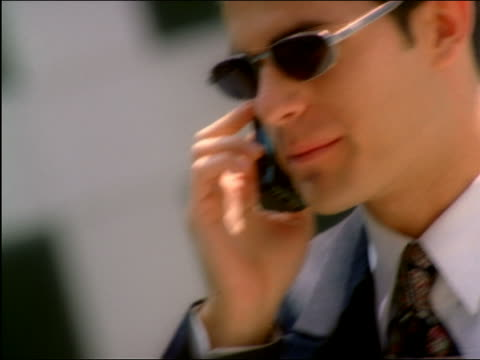 canted close up businessman in sunglasses talking enthusiastically on cellular phone outdoors - yuppie stock videos and b-roll footage