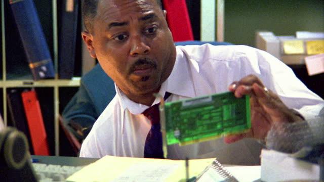 stockvideo's en b-roll-footage met close up businessman kneeling behind desk / looking at circuit board - it'er