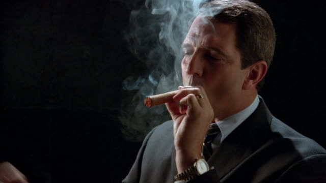 close up businessman lighting cigar/ taking puffs on cigar and smiling/ zoom in looking at camera - sigaro video stock e b–roll
