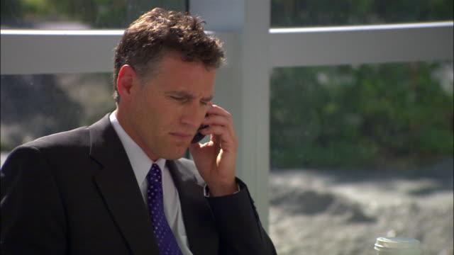 Close up businessman on phone near window/ Seattle