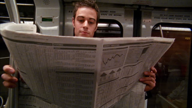 vídeos de stock e filmes b-roll de close up businessman reading financial pages of newspaper on subway - jornal