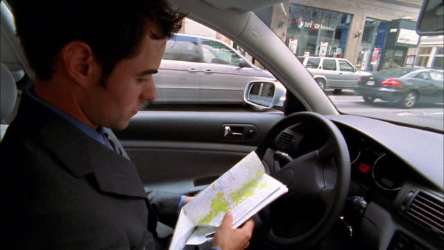 Close up businessman sitting in parked car, unfolding map / looking at map / traffic in background