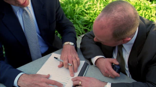 Close up businessman watching other businessman signing document outdoors