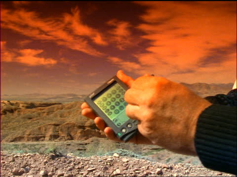 stockvideo's en b-roll-footage met close up businessman's hands using personal data assistant with desert hills in background / orange filter - elektronische organiser