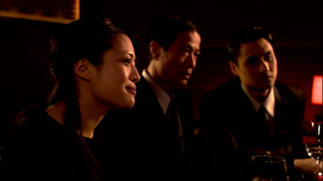 close up businesspeople translating for man at dinner meeting - 言語翻訳点の映像素材/bロール