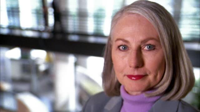 vídeos y material grabado en eventos de stock de close up businesswoman on office catwalk looking at cam - 50 59 años