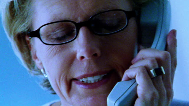 BLUE close up businesswoman with eyeglasses talking on telephone looking serious + taking off glasses
