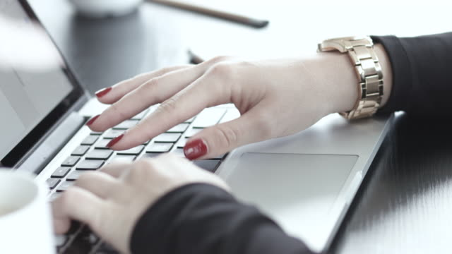 Close up, businesswoman with red nails types on laptop