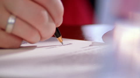 close up businesswoman's hands signing document / contract - paperwork点の映像素材/bロール