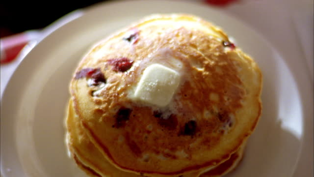 close up butter melting on a stack of pancakes / jug pouring syrup on pancakes - melting butter stock videos & royalty-free footage
