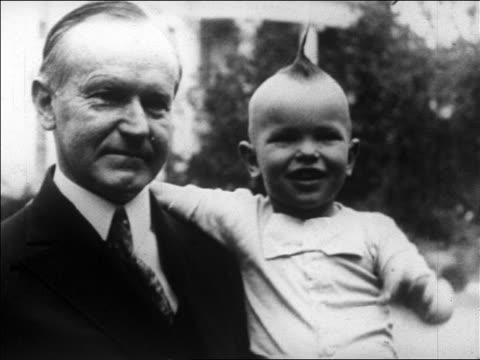 B/W 1927 close up Calvin Coolidge holding child star Baby Snookums who waves to camera / newsreel