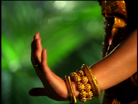 """close up Cambodian woman's hands in native dress doing native dance in """"jungle"""""""