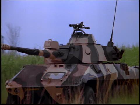 close up camouflage army tank moving towards camera in field / rio de janeiro, brazil - 装甲車点の映像素材/bロール