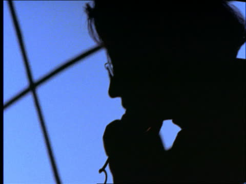 close up CANTED silhouette of businesswoman talking on phone in front of window