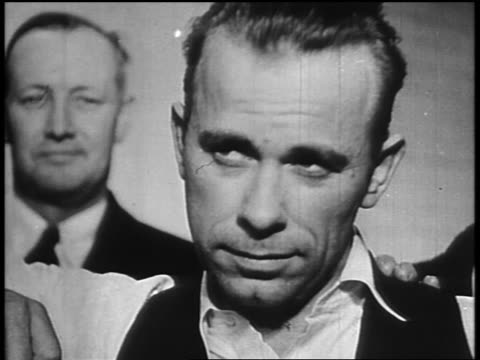 b/w 1934 close up captured john dillinger posing / man in background - john dillinger stock-videos und b-roll-filmmaterial