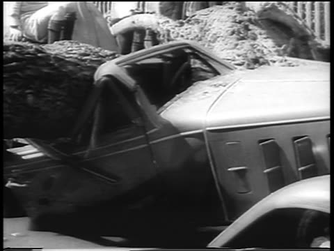 B/W 1938 close up car crushed by tree after hurricane / Northeast US / newsreel