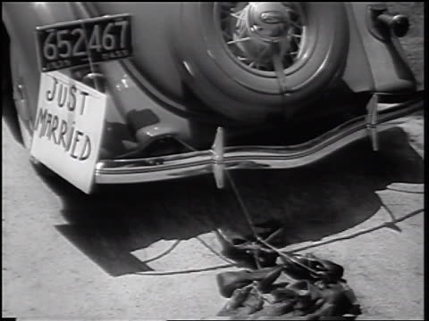"b/w 1935 rear view close up car with ""just marrried"" sign + string of shoes pulling away - 1935 stock videos & royalty-free footage"
