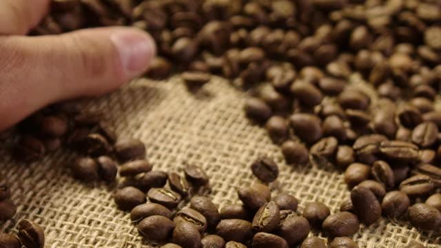 クローズ アップ コーヒー豆 4 k スローモーションを caressing - 麻袋点の映像素材/bロール