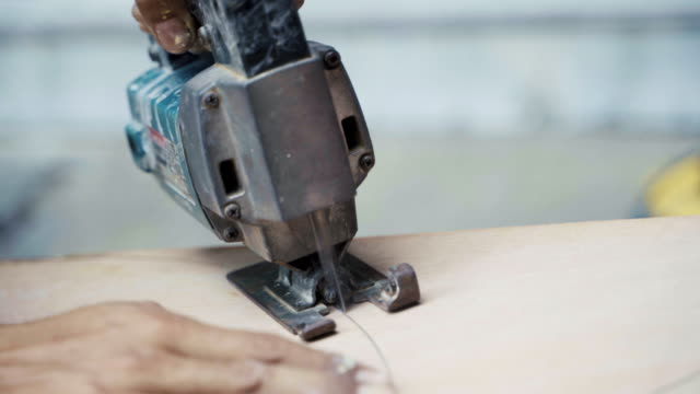 close up carpenter's hand using jigsaw blade cuts the circle wood. - deposito di legname video stock e b–roll