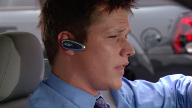 close up carpool driver wearing bluetooth ear piece / pan to passenger talking to him - headset stock videos & royalty-free footage