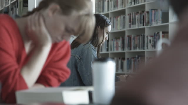 stockvideo's en b-roll-footage met close up, caucasian woman tries to study in library - scherpte verlegging
