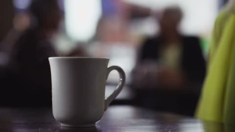 close up ceramic cup of coffee is picked up by a woman in a coffee shop. - coffee cup stock videos & royalty-free footage