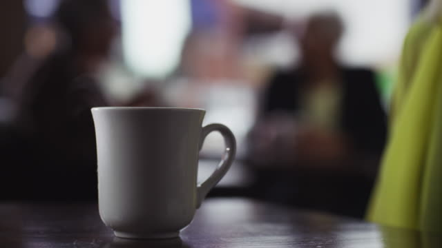 stockvideo's en b-roll-footage met close up ceramic cup of coffee is picked up by a woman in a coffee shop. - reiken