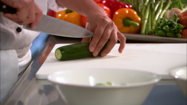 close up chef slicing zucchini on cutting board / rack focus placing chopped zucchini in bowl / auckland - courgette stock videos and b-roll footage
