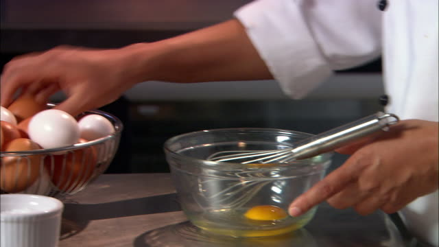 close up chef taking two eggs from basket, cracking into glass bowl and beating with whisk / auckland - wire whisk stock videos and b-roll footage
