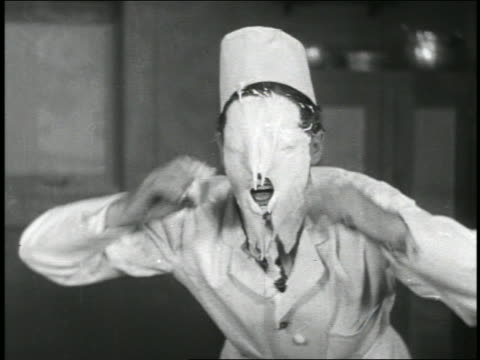 vídeos de stock, filmes e b-roll de b/w 1920 close up chef wiping pie from face after pie fight / short - pie humano