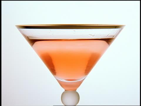 vídeos y material grabado en eventos de stock de close up cherry dropping in pinkish/orange drink (cosmopolitan) in martini glass - sección alta