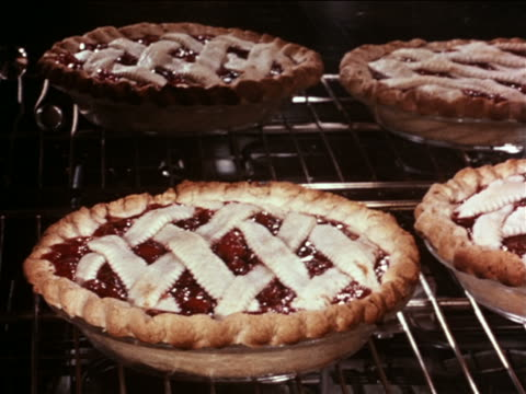 1960 close up cherry pies + reflection of pies bubbling in oven / industrial