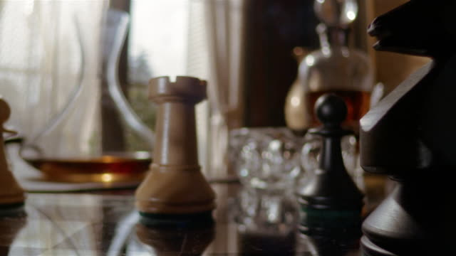 Close up chess game / hand picking up snifter of brandy / dolly shot hand knocking over chess piece with knight