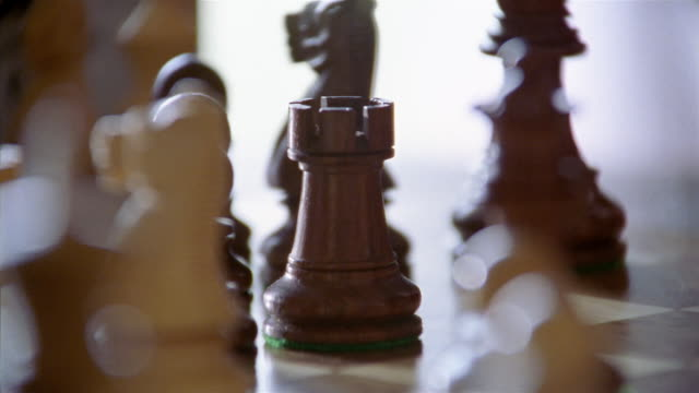 close up chess pieces / hand moving knight / taking rook / using rook to stop timer on chess clock - chess stock videos & royalty-free footage